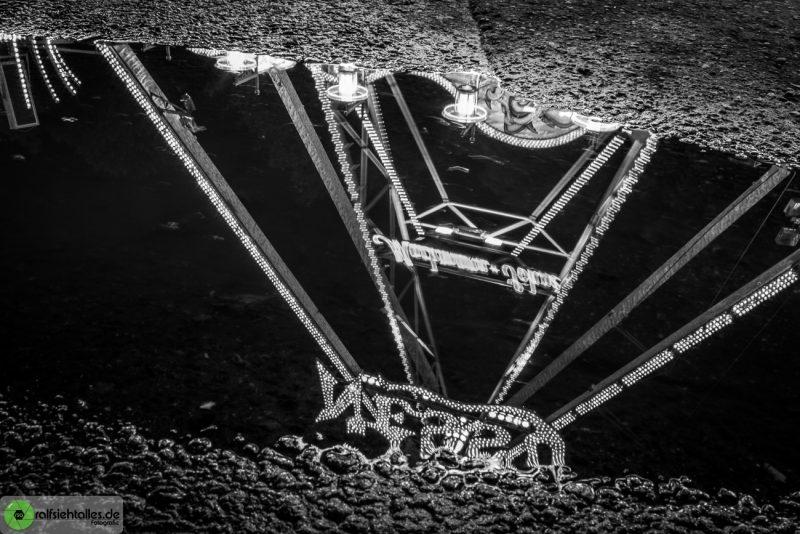 Spiegelung der Nessy Schiffsschaukel in einer Pfütze