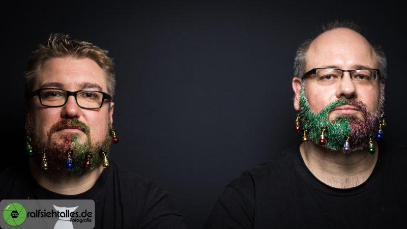 Tim und Ralf ernst beim Weihnachtsshooting mit Glitzerbärten und Weihnachtskugeln