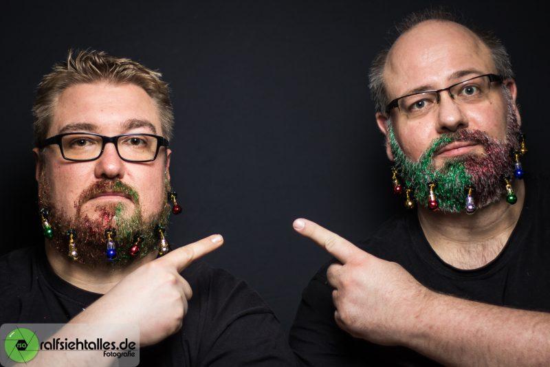 Tim und Ralf mit Glitzerbärten und Weihnachtskugeln